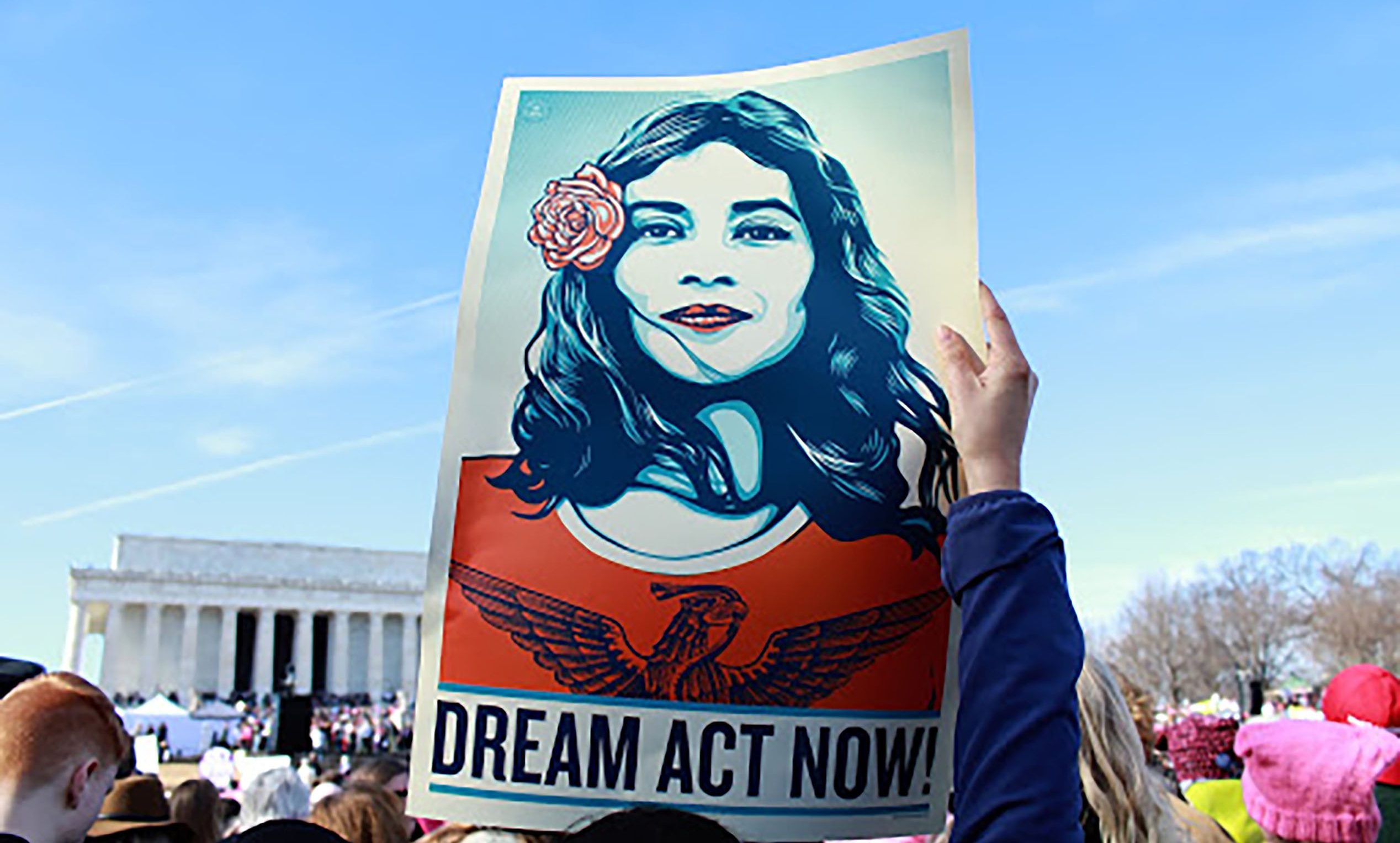 Woman holding a poster with text: Dream Act Now!